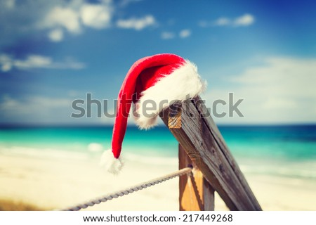 beach, summer, vacations, christmas and sea concept - close up of santa helper hat on beach - stock photo