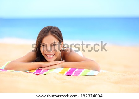 Beach summer woman sunbathing enjoying sun smiling lying down on towel looking away. Beautiful pretty cute multiracial Asian Caucasian girl in her 20s on vacation travel holidays. - stock photo
