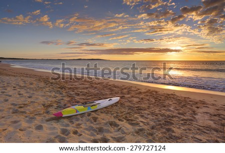 Beach sunrise and paddleboard on the sand  at shoreline. - stock photo