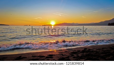 Beach Sunset - Photograph taken at English Bay in Vancouver, British Columbia, Canada. - stock photo