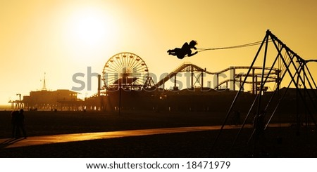 Beach sunset scene with person on a swing infront of a pier - stock photo
