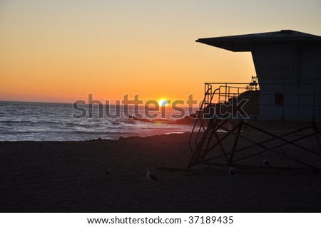 Beach Sunset with Lifeguard Tower (red flare) - stock photo