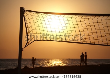 Beach sunset with silhouette of people and beachball net in foreground. - stock photo