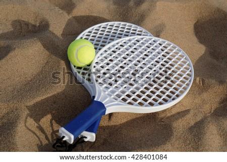 Beach tennis rackets and ball on sand - stock photo