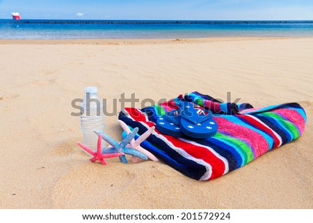 beach towel and bottle of cool water on sandy beach by sea side - stock photo
