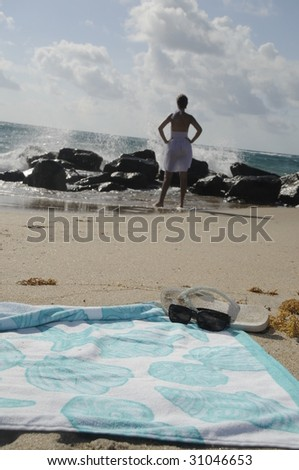 Beach towel and sunglasses, with woman in sand off in the distance - stock photo