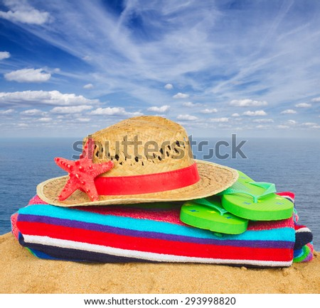 beach towel, straw hat and  green sandals on sand by sea shore - stock photo