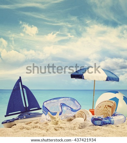 Beach toys on sandy beach with blue sea in background - stock photo