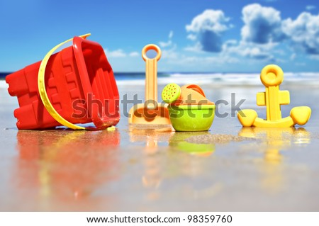 Beach toys on the beach with sea in the background - stock photo