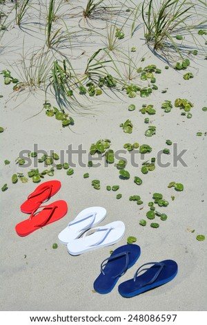 Beach travel concept. Red white and blue flip flops on the sand, perfect for cover art.