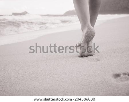 Beach travel - Girl walking on sandy beach leaving footprints in the sand. Closeup detail of female feet and sandy beach in Hawaii. - stock photo