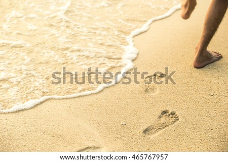 Beach travel - Man walking on sand beach leaving footprints in the sand. Closeup detail of male feet and golden sand