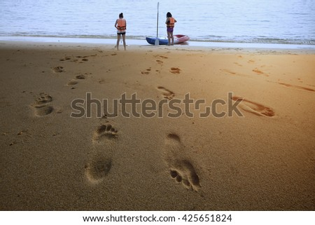 Beach travel - The two young tourists walking on sandy beach leaving footprints in the sand.  - stock photo