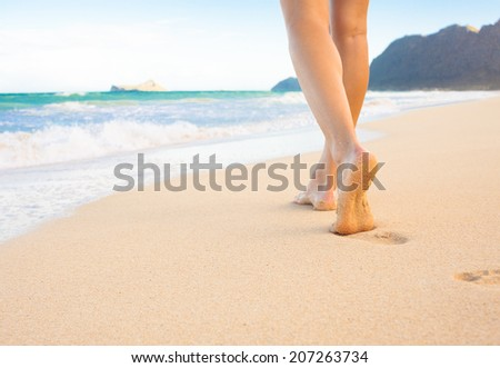 Beach travel - woman walking on beach leaving footprints in the sand. Closeup detail of female feet and golden sand at the beach in Hawaii, USA. - stock photo