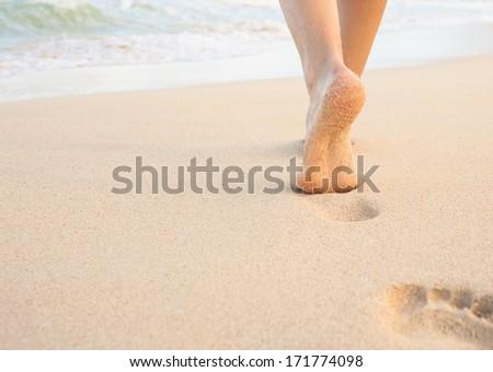 Beach travel. Woman walking on sand beach leaving footprint in the sand. - stock photo