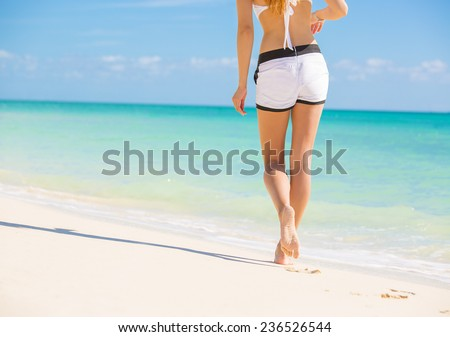 Beach travel. Woman walking on sand beach leaving footprints in the sand. Closeup detail female feet and white sand on Bahamas beach caribbean destination vacation getaway.  Tourism, leisure concept - stock photo