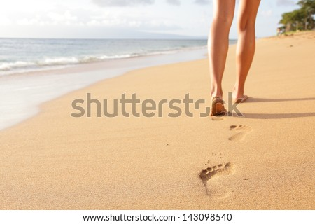 Beach travel - woman walking on sand beach leaving footprints in the sand. Closeup detail of female feet and golden sand on Kaanapali beach, Maui, Hawaii, USA. - stock photo