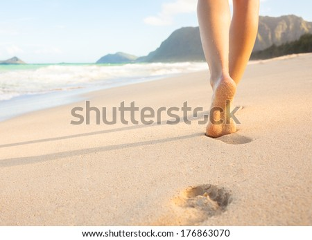 Beach travel - woman walking on sand beach leaving footprints in the sand. Closeup detail of female feet and golden sand on beach in Hawaii. - stock photo