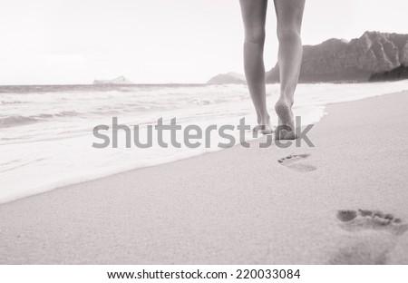 Beach travel - Woman walking on sand beach leaving footprints in the sand. Closeup detail of female feet and sandy beach in Hawaii - stock photo
