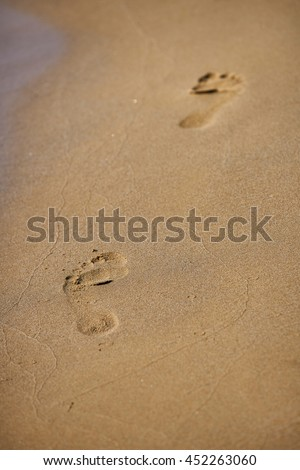 Beach travel - woman walking on sand beach leaving footprints in the sand. Closeup detail of female feet and golden sand on beach