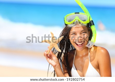 Beach travel woman with snorkel and starfish on vacation in bikini enjoying summer vacation holidays on tropical resort by ocean sea. Beautiful young mixed race Asian Caucasian woman smiling happy. - stock photo