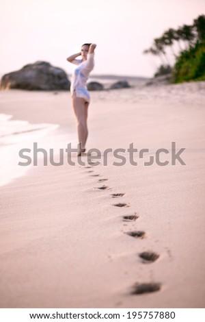 Beach trip - young girl walking on the sandy beach leaving footprints - stock photo