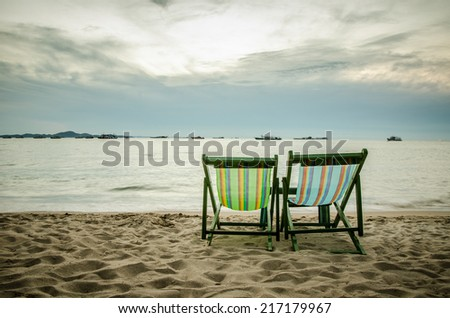beach, two deck chairs and blue sky