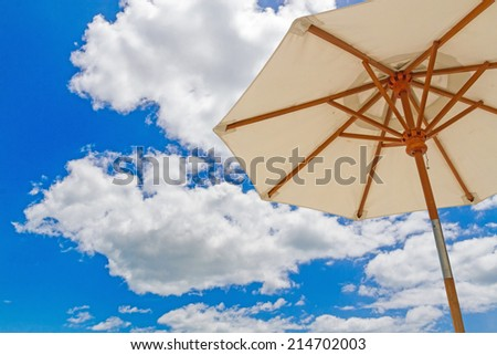 Beach umbella  on blue sky with clouds