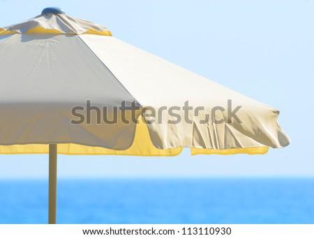 Beach umbrella against the sea and sky - stock photo