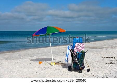 Beach Umbrella and Cart on White Sandy Beach - stock photo