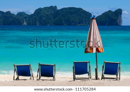 Beach Umbrella and chairs on Koh Phi Phi Island in Thailand - stock photo