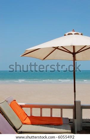 Beach umbrella and orange towel - stock photo