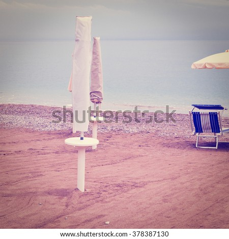 Beach Umbrella and Sun Bed in the Sandy Coast near the Italian City of Minori, Instagram Effect - stock photo