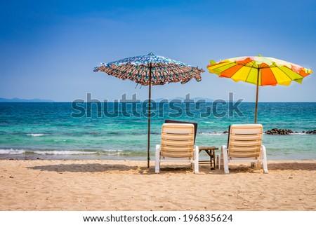 Beach umbrella and sunbath seats and side table are on sand beach - stock photo