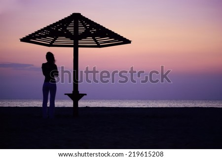 Beach umbrella and the girl silhouette on sunset - stock photo