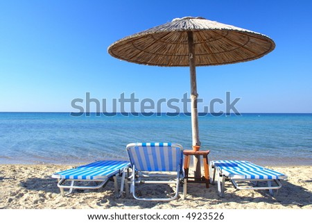 beach umbrella and three chairs in Greece - stock photo