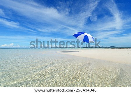 Beach umbrella on a sunny beach with the blue sea in the background. - stock photo