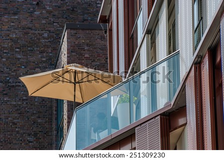 Beach umbrella on an apartment patio Hamburg Germany Sunshade or beach umbrella on a modern apartment patio with glass enclosure for a healthy outdoor lifestyle, view from below - stock photo