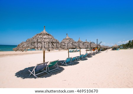 Beach umbrellas and deck chairs in front of the My Khe beach in Da Nang, Vietnam