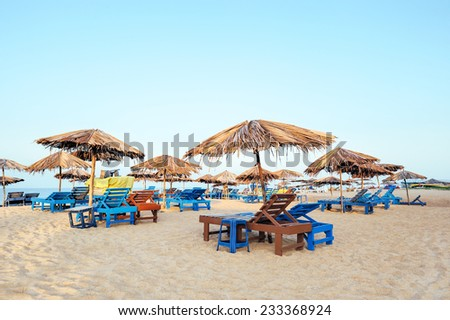 Beach umbrellas and deckchair on the tropical coast in Goa, india - stock photo