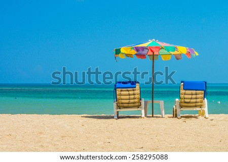 Beach umbrellas and sunbathe seats on Phuket sand beach in Southern Thailand