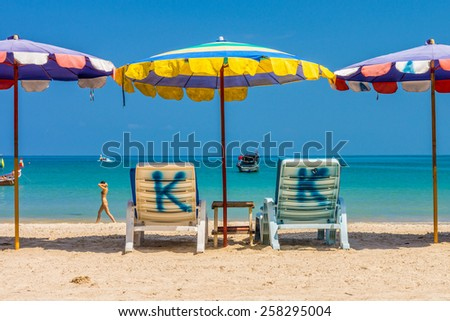 Beach umbrellas and sunbathing seats on Phuket sand beach in Southern Thailand - stock photo