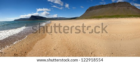 Beach under the mighty fjords rising from the sea in the Westfjords Peninsula, northwestern Iceland - stock photo
