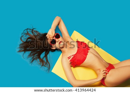 Beach Vacation abstract concept. Colorful studio portrait of young Fashion Woman in red swimsuit and sunglasses. Isolated on Blue background like sea water - stock photo