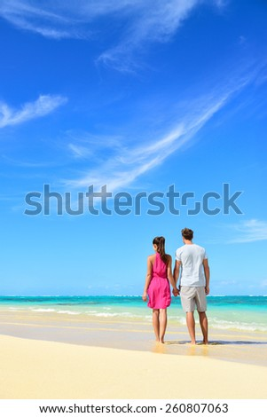 Beach vacation couple relaxing on summer holidays. Young people standing from behind holding hands looking at the ocean, vertical crop with a lot of copy-space in the blue sky. Travel concept.