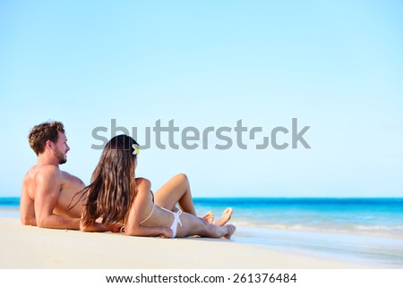 Beach vacation couple relaxing tanning in summer. Beautiful young adults on holidays lying down on white sand enjoying travel getaway under blue sky by turquoise water ocean sea. Multiracial couple. - stock photo
