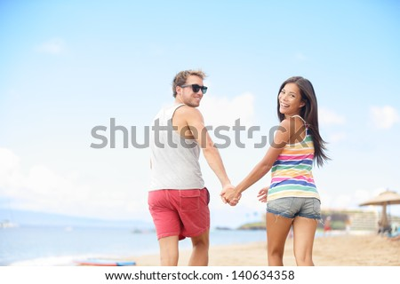 Beach vacation fun with cool trendy hipster couple. Two people running playful holding hands on summer travel holidays. Multi-ethnic interracial young couple, Asian woman, Caucasian man at ocean sea. - stock photo