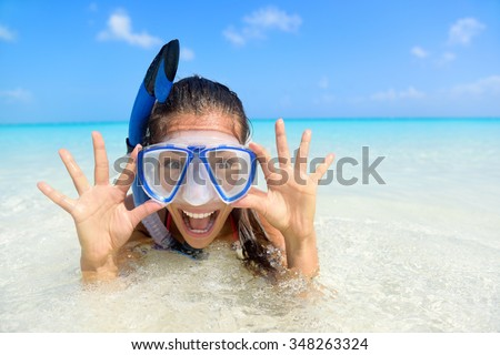 Beach vacation fun woman wearing a snorkel scuba mask making a goofy face while swimming in ocean water. Closeup portrait of Asian girl on her travel holidays. Summer or winter destination. - stock photo