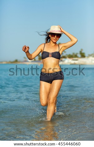 Beach vacation. Young woman in a hat and swimsuit walking on the beach on a hot summer day