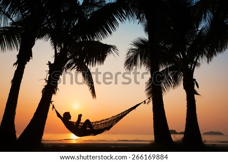 beach vacations, silhouette of woman reading in hammock  - stock photo